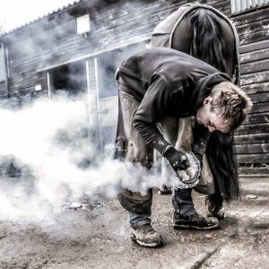 Farrier Shoeing a Horse